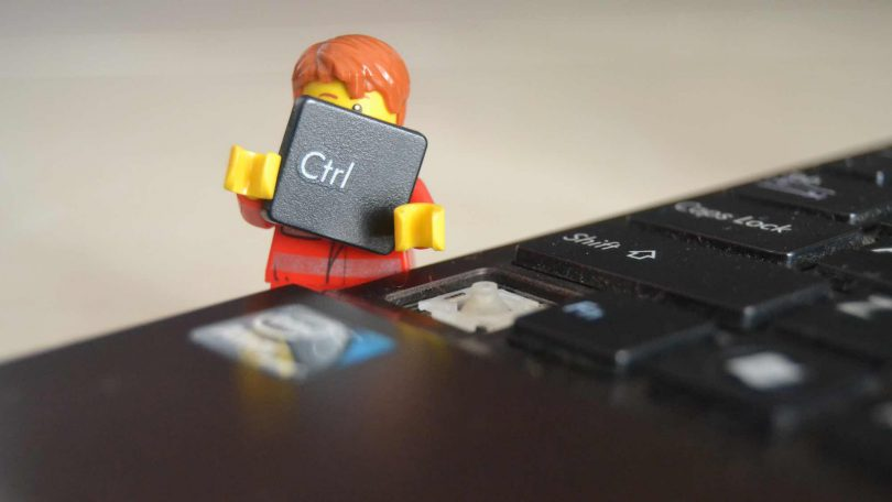 Lego minifig character holding the 'Ctrl' key from a laptop keyboard